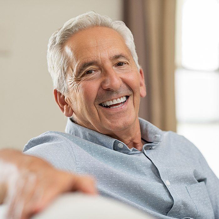 Older man sharing smile with natural looking denture