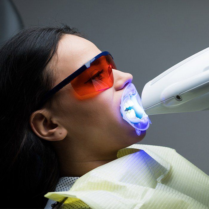 Woman receiving zoom in office teeth whitening treatment