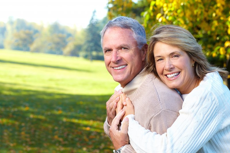 Older couple smiling and hugging after visiting a cosmetic dentist.