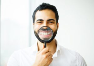 man using magnifying glass to show off his cosmetic dentistry work