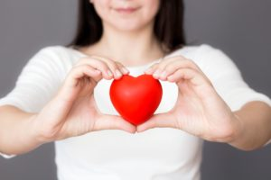 woman holding a red love heart for American Heart Month